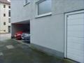 Zufahrt mit überdachten Stellplätzen und Garage