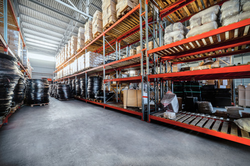 warehouse-industrial-goods-large-long-racks-cardboard-boxes-and-coiled-plastic-tube-toning-the-image
