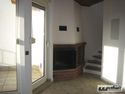 Wohnzimmer mit Kamin und Zugang zur Loggia