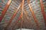 Das offene Dachgebälk des Walmdaches mit Schiefreindeckung