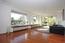 Der Wohnraum mit hellem, versiegeltem Eicheparkettboden - große Fensterflächen und die wandhohe Schiebetür zum Garten lassen viel Licht herein