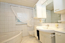 Raumhoch hell gefliestes Elternbad mit Eckwanne und Badmöblierung - direkter Zugang vom Elternschlafraum