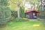 Gartenhaus aus Holzbalkenlagen, dahinter Blechgerätehaus