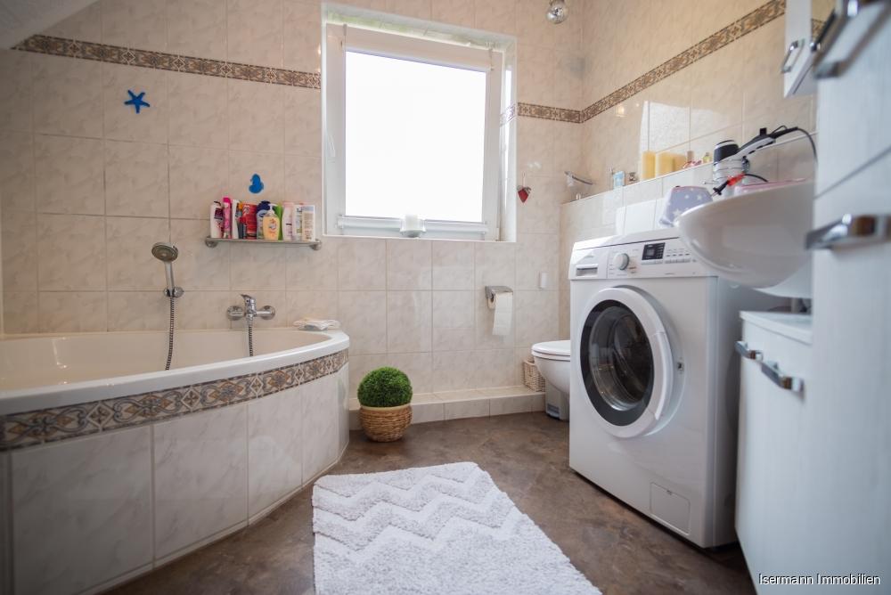Das hell geflieste Badezimmer ist mit einer Eckwanne ausgestattet.