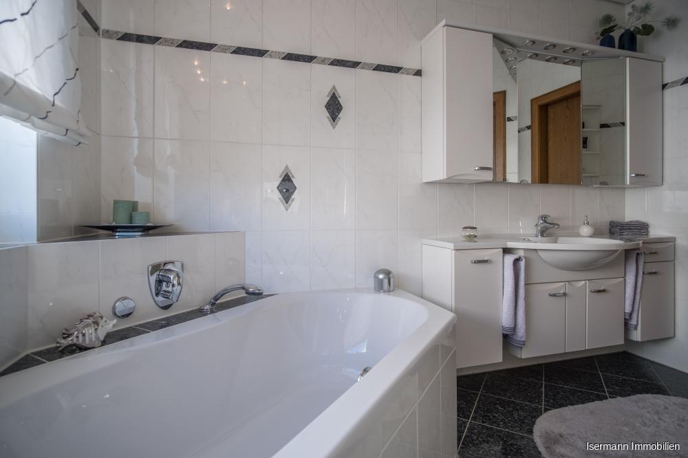 Das Badezimmer ist weiß gefliest...