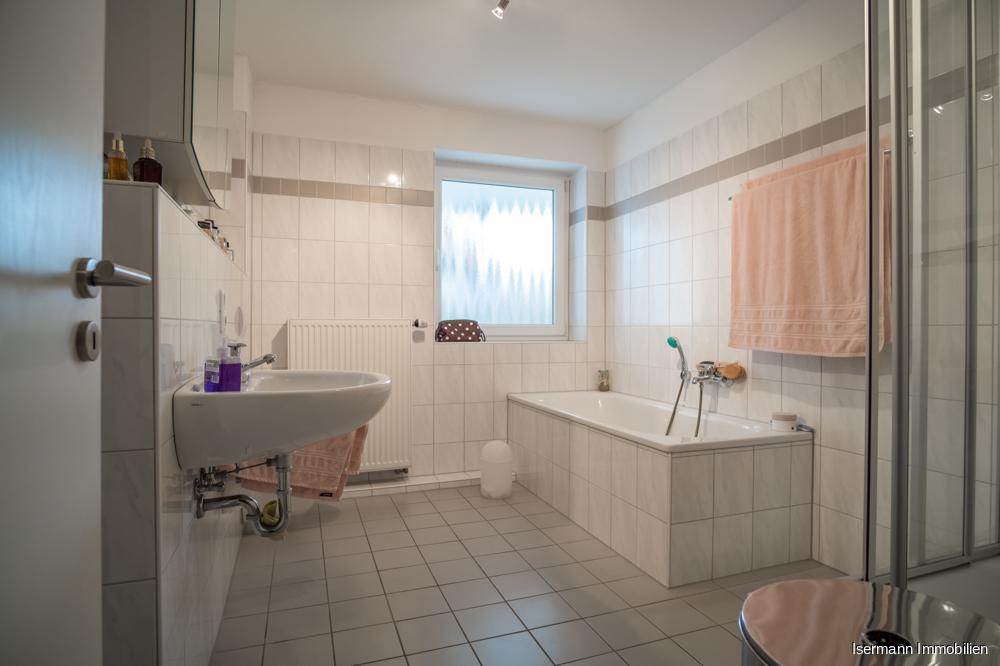 Das hell geflieste Tageslichtbad verfügt über eine Wanne und eine Dusche.