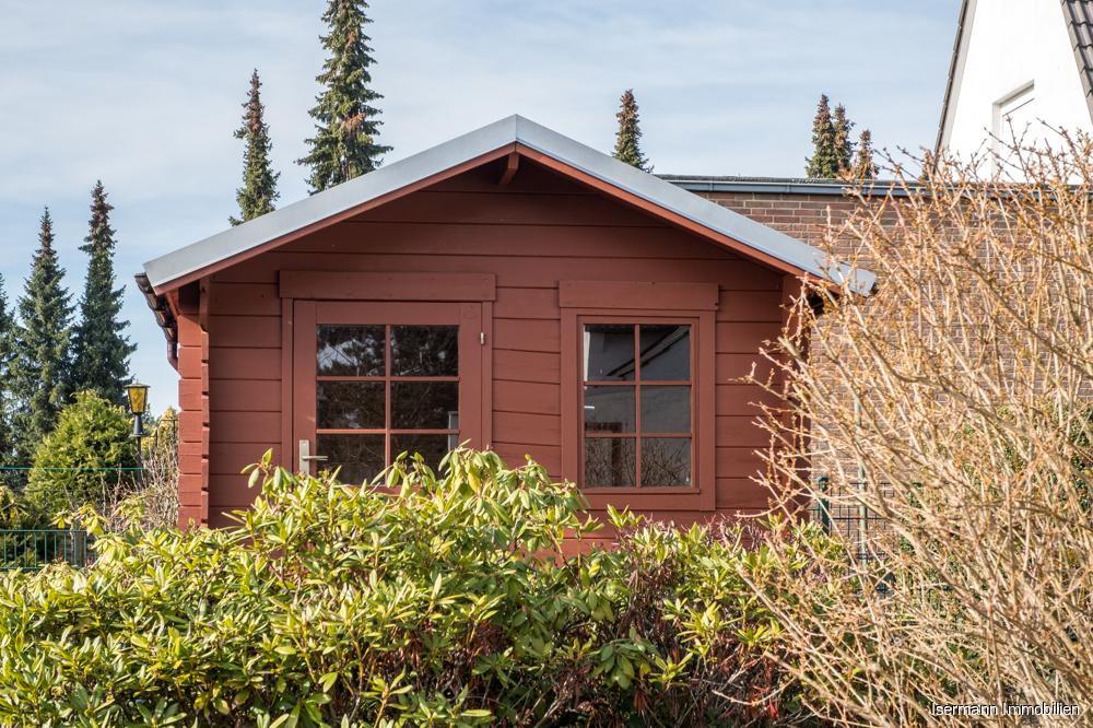 Das hübsche Gartenhaus bietet Platz für Gartengeräte.