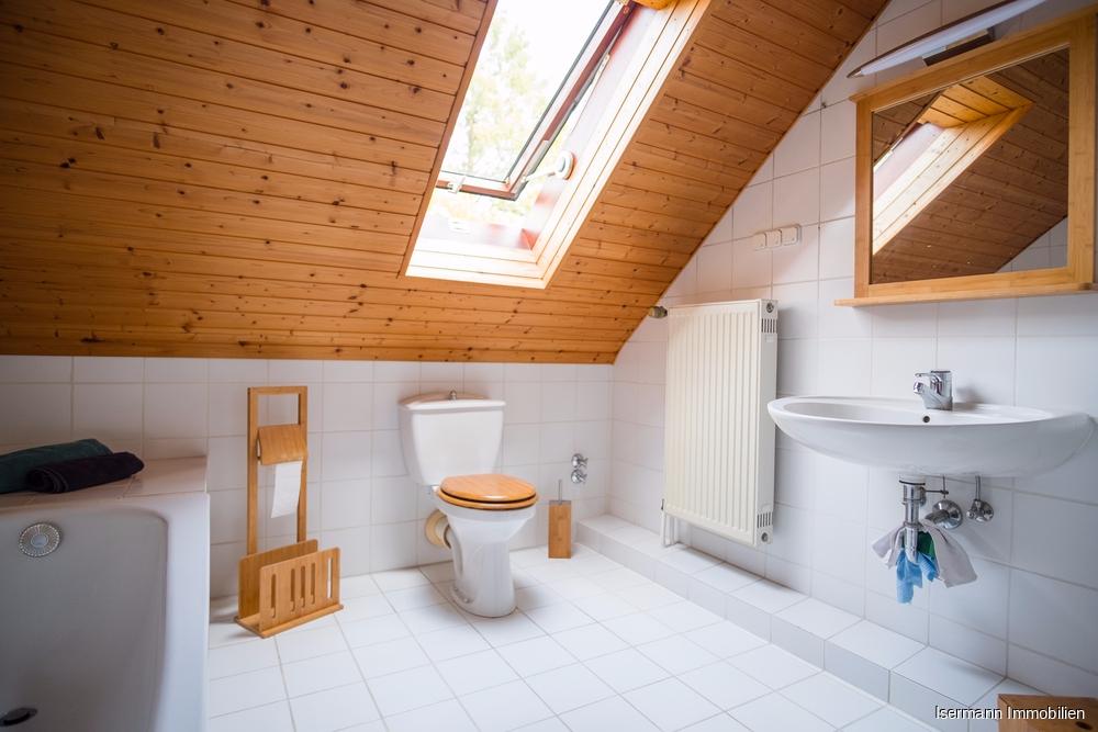 Das weiß geflieste Bad ist mit einer Wanne und Dusche ausgestattet.