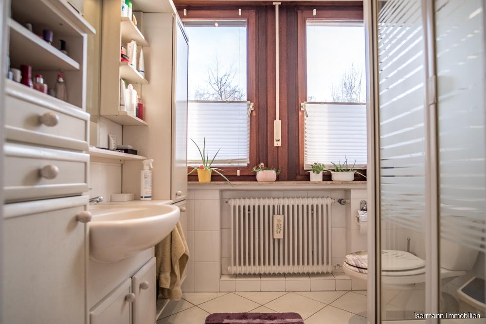 Das hell geflieste Kinderbad besitzt eine Dusche.