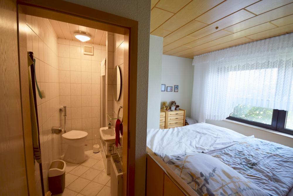 Schlafzimmer mit WC-Dusche in einem Raum