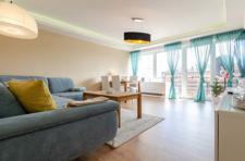 Wohnzimmer mit neuwertiger Fensterfront und Zugang Loggia