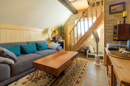 Urig sind hier nicht nur die Holzpaneelen an der Wand und die Sichtbalken an der Decke, sondern auch die Holztreppe in den Spitzboden.
