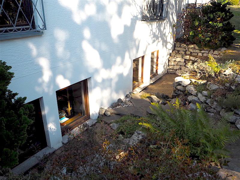 Natursteinmauer vor den Souterrainzimmern