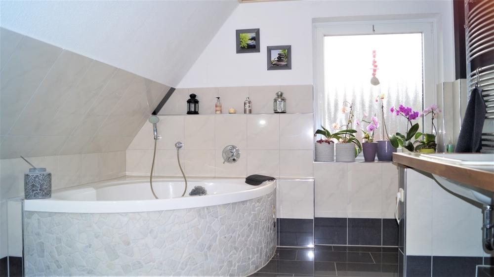 Zeitlos, modernes Badezimmer im Obergeschoss mit Eckwanne und Waschtisch