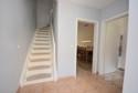 weiße Holztreppe ins Obergeschoss