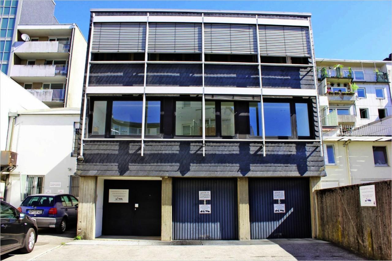 Gebäuderückansicht mit 2 Garagen u. mehreren Stellplätzen