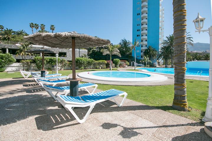 Poolbereich mit Liegen und Sonnenschirmen