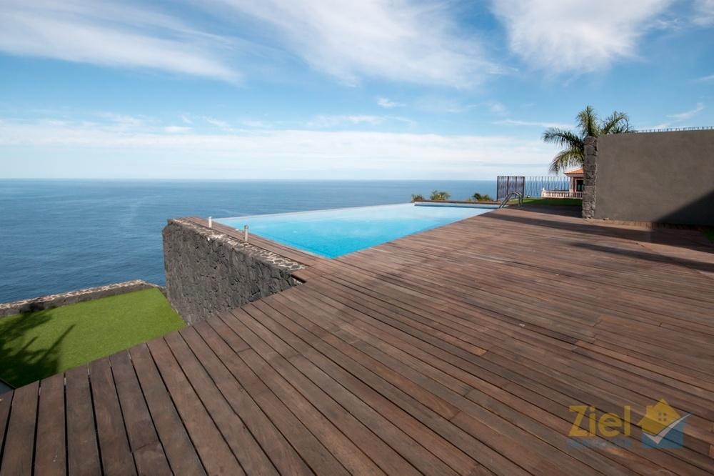Eine hochwertige Holzterrasse umgibt den Pool