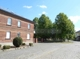Haus, Einfahrt und Grünfläche mit Baumbestand